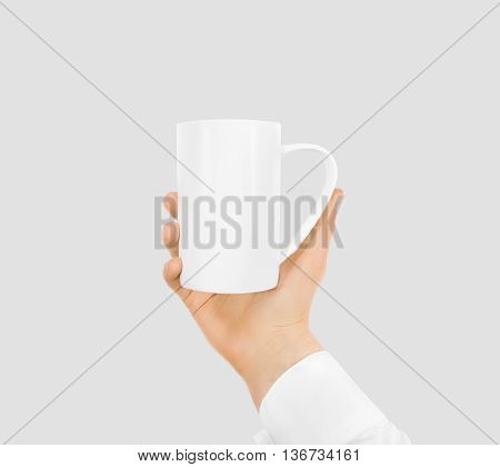 White blank mug mock up holding hand isolated. Empty ceramic tea cup hold handle. Clear drink mug mockup ready for logo design presentation. Teacup pot holder.