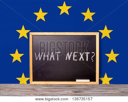 Brexit UK EU referendum concept for out of Great Britain from rest European union and handwriting text what next written in chalkboard on flag background close up