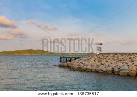 Lifeguard stand over rocky coastline with mountain background