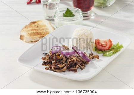 gyros meat on a plate with red wine