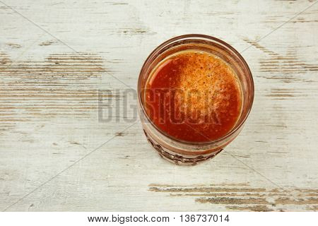 Gass of fresh tomato juice on a wooden countertop in vintage style. Flat horizontal view.