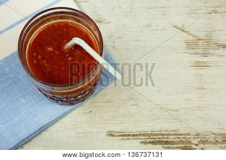 A glass of fresh tomato juice with a straw standing on a napkin and an old wooden table in vintage style. Flat horizontal view.