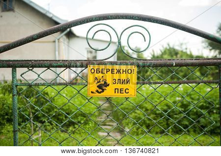 Carefully, evil dog. Sign hanging on a metal fence