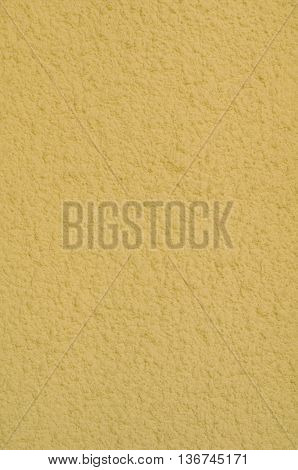 Background of a yellow stucco coated and painted exterior rough cast of cement and concrete wall texture decorative coating