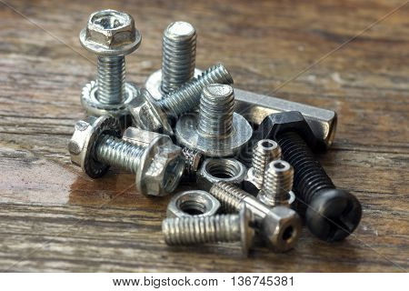 metal screw nut bolt on wood background