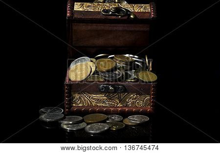 old coins in chest on black background with reflections