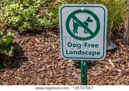 A sign posted to prohibit access of dogs on the landscaping.