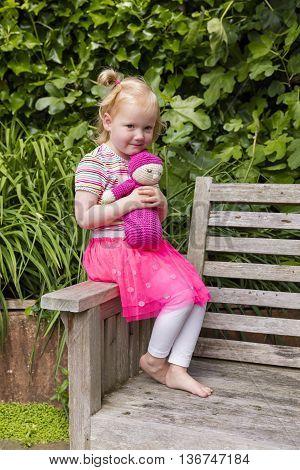 Little Girl Holding Homemade Crochet Doll In The Garden