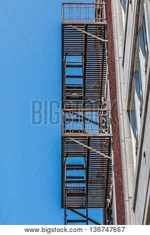 Bottom view of a fire escape attached to the side of a residential building.