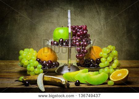 Still life with assorted summer fruits,yellow and red grapes,cantaloupe, oranges, cherries,green apple and banana on wooden table