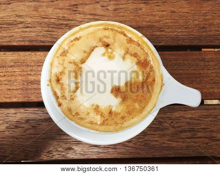 a cup of specialty coffee on a wooden table with a white space to write something in the middle.