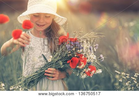 Girl and the Corn Poppy. Summer Meadow Outdoor Fun. Smiling Caucasian Girl with Wildflowers Bouquet.