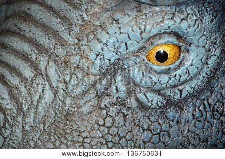 Close up of a yellow eye of a replica dinosaur