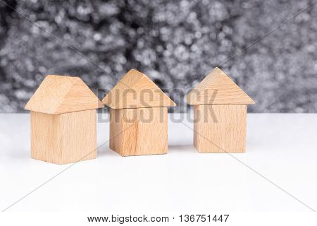 Three houses made of wooden blocks with a blurry background