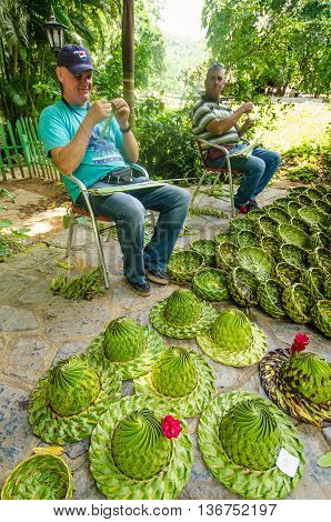 VALLE DE VINALES - CUBA JUNE 18, 2016: Cuban men weave palm leaves to make attractive baskets for sale to tourists visiting the famous caves at Cueva del Indio in the San Vicente Valley.