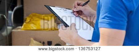 Courier's Hand Writing On Clipboard