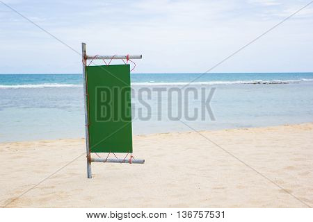 Blank green Sign on a pole Sea side