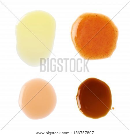 Four puddles of hot pepper, worchester sauce, olive oil and wine vinegar, isolated over the white background