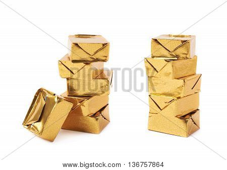 Stack of mulitple bouillon stock broth cubes wrapped in golden foil, composition isolated over the white background, set of two different foreshortenings