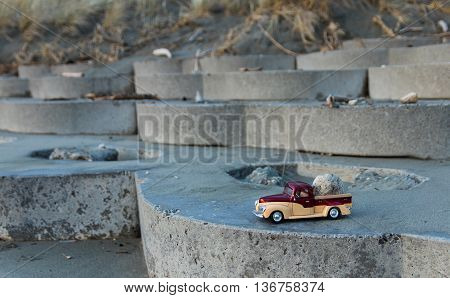 Model truck with a pumice rock on it parked on a beach front steps blocks.