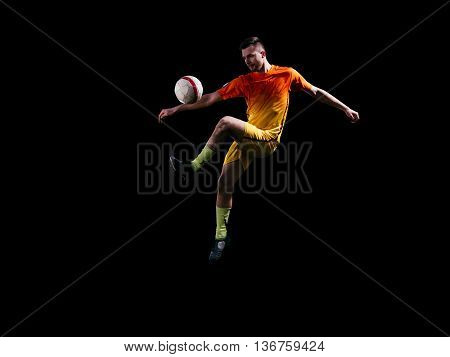 Professional soccer player in red kicking ball in jump on black background