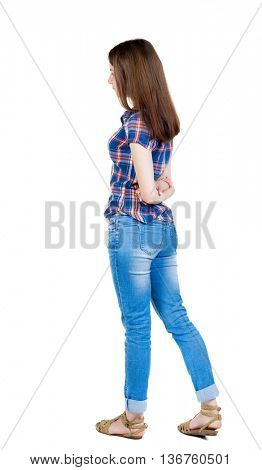 back view of standing young beautiful  woman.  girl  watching. Rear view people collection.  backside view of person.  Girl in a blue plaid shirt with short sleeves is hands clasped behind his back.