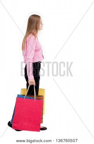 ack view of going  woman  with shopping bags . beautiful girl in motion.  backside view of person. Isolated over white background. The girl in the pink shirt is left bent under weight of the bags.