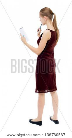 back view of  stands woman takes notes in a notebook. girl  watching. Rear view people collection. Isolated over white background. Blonde girl in a burgundy dress thoughtfully looks in a notebook.