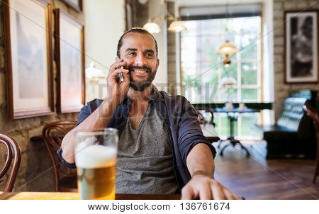 people, communication and technology concept - happy man calling on smartphone and drinking beer at bar or pub