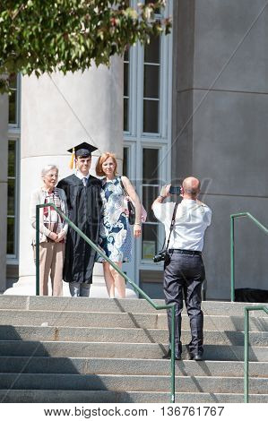 ATHENS, GA - MAY 2016: A male graduate poses with family members for a photo before the graduation ceremony at the University of Georgia in Athens GA on May 13 2016.