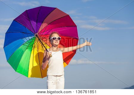 Ten girl with umbrella standing on the beach at the day time.