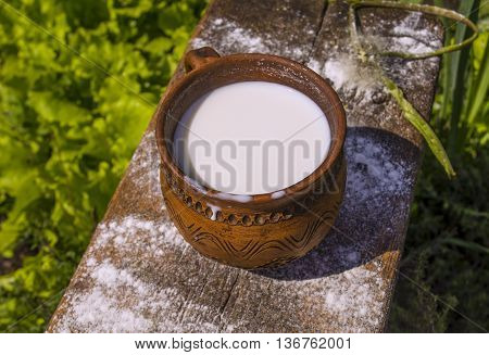 Milk in  mug on wooden table.  Milk in vintage cup on old wooden table