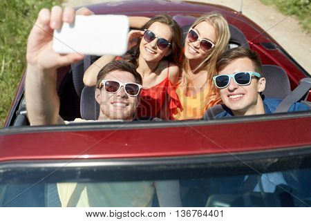 leisure, road trip, travel and people concept - happy friends driving in cabriolet taking selfie by smartphone at country
