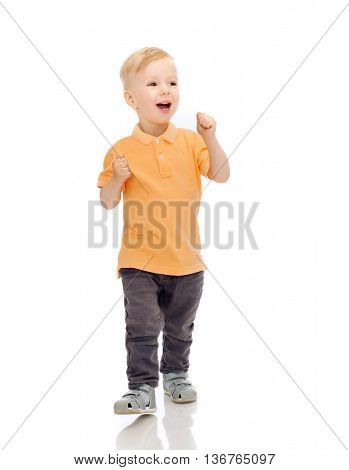 childhood, fashion, emotion, expression and people concept - happy little boy in casual clothes having fun