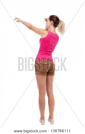 Back view of  pointing woman. beautiful girl. Rear people collection.  backside of person.  Isolated over white background. Blonde in brown shorts saw something interesting on the left.