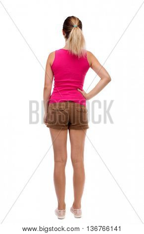 back view of standing young beautiful  woman.  girl  watching. Rear people collection.  backside of person.  Blonde girl in shorts and a pink blouse is resting his hand in his left side.