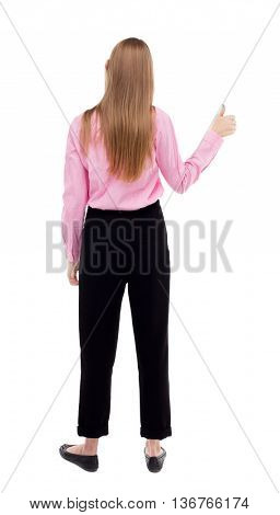 Back of  woman thumbs up. Rear people collection. backside view of person. Isolated over white background. The girl office worker in black trousers shows thumb up with his left hand.