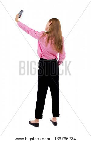 back view of standing young beautiful  woman  and using a mobile phone. girl  watching. Rear people collection.  backside of person.  Isolated over white background.  Turning right takes girl self