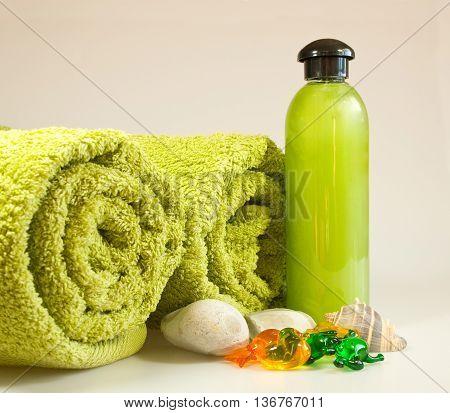 Bath accessories in green colour, towels, shampoo and bath oil