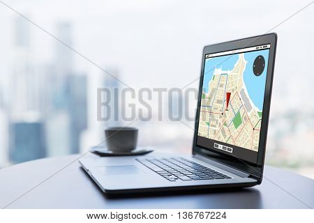 technology, location, navigation, business and modern life concept- close up of open laptop computer with gps navigator map on screen and coffee cup on table at office or hotel room