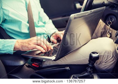 transport, business trip, technology and people concept - close up of young man with laptop computer driving car