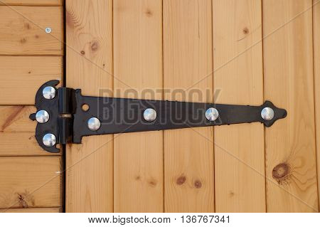 Metal figured door loop on a wall of pavilion with wooden finishing
