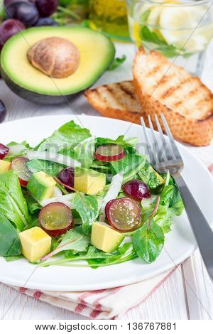 Vegetarian salad with avocado grape rucola onion with vinegar dressing on white plate vertical
