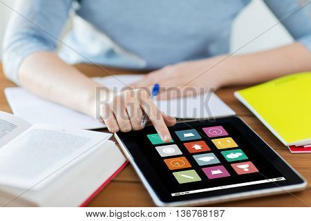 business, education, technology, media and people concept - close up of student woman with menu icons on tablet pc computer screen and notebook at home