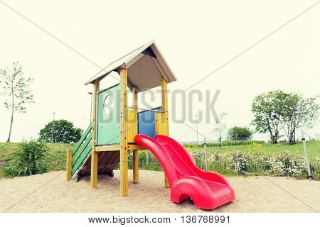 childhood, equipment and object concept - slide on playground outdoors