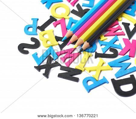 White surface covered with the multiple colorful cmyk painted wooden letters with the drawing pencils over it, composition as a backdrop composition