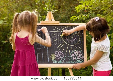 girl paint on a board house sun tree. girls in nature
