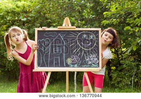 girls paint on a board house sun tree. girls in nature