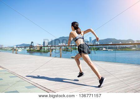 Sporty woman running on boardwalk