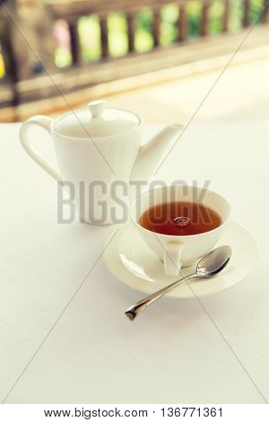 drinks, relaxation and tea party concept - tea-set of cup, pot, spoon and saucer at teahouse
